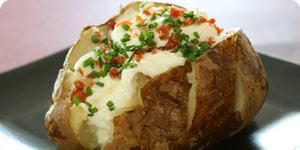 Green toppings on baked potato