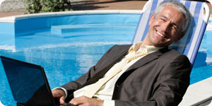 Businessman relaxing beside a pool