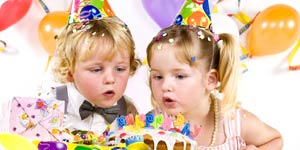 Two kids blowing cake candles