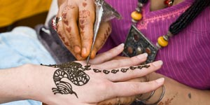Girl getting henna tattoo on her hand