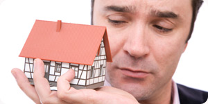 Man holding a miniature model house