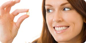 Woman holding a vitamin capsule