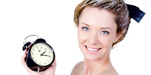 Woman holding clock while bleaching hair