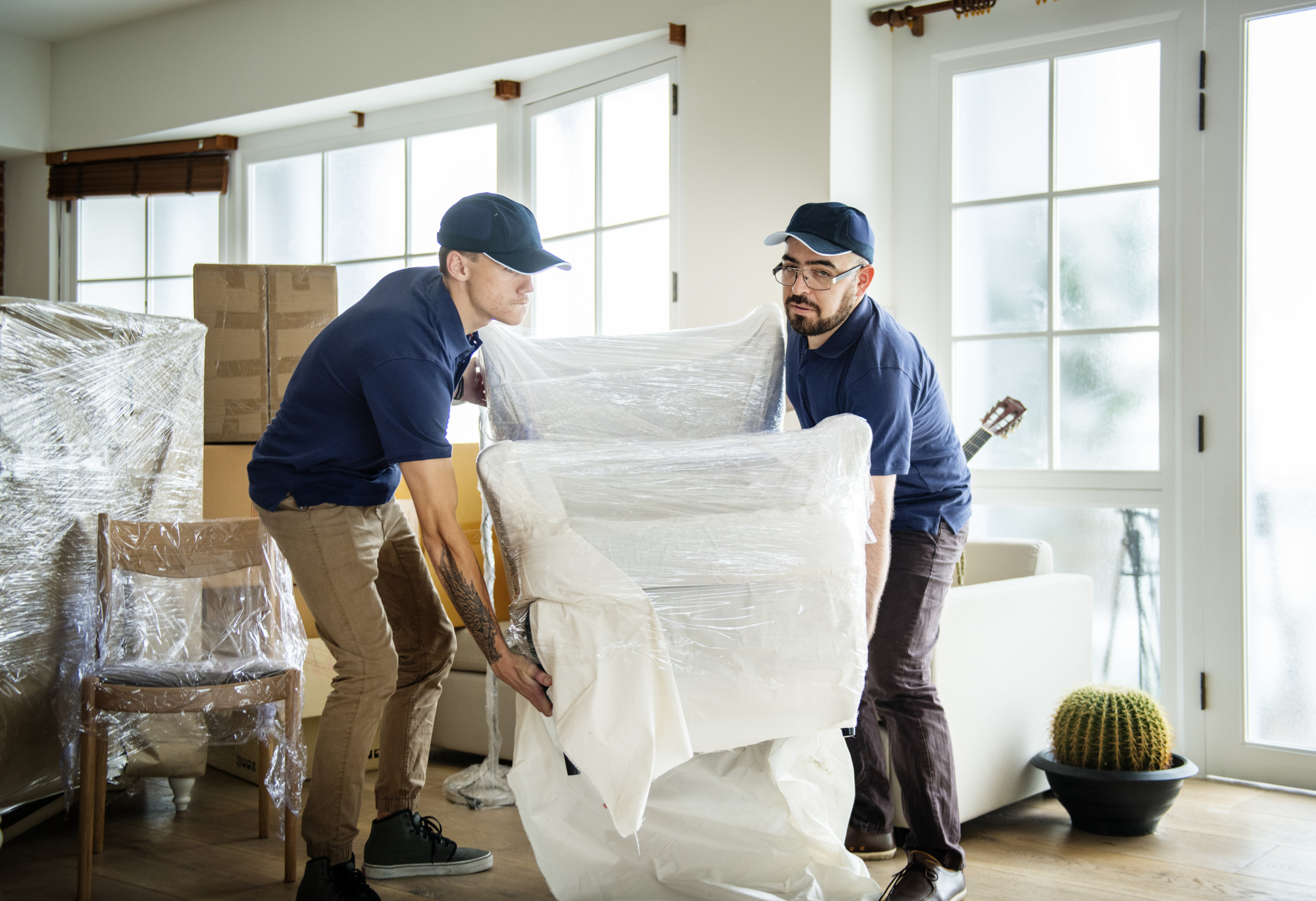 two movers carrying furniture