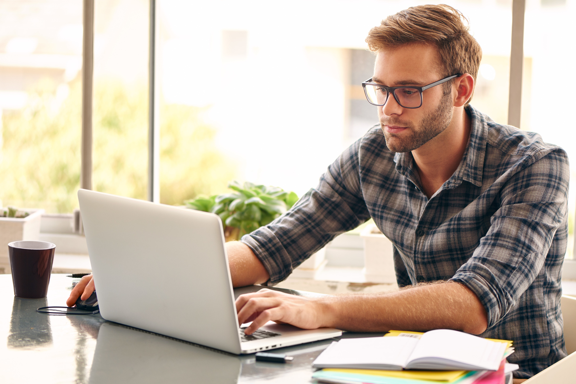 young man with glasses typing on his laptop