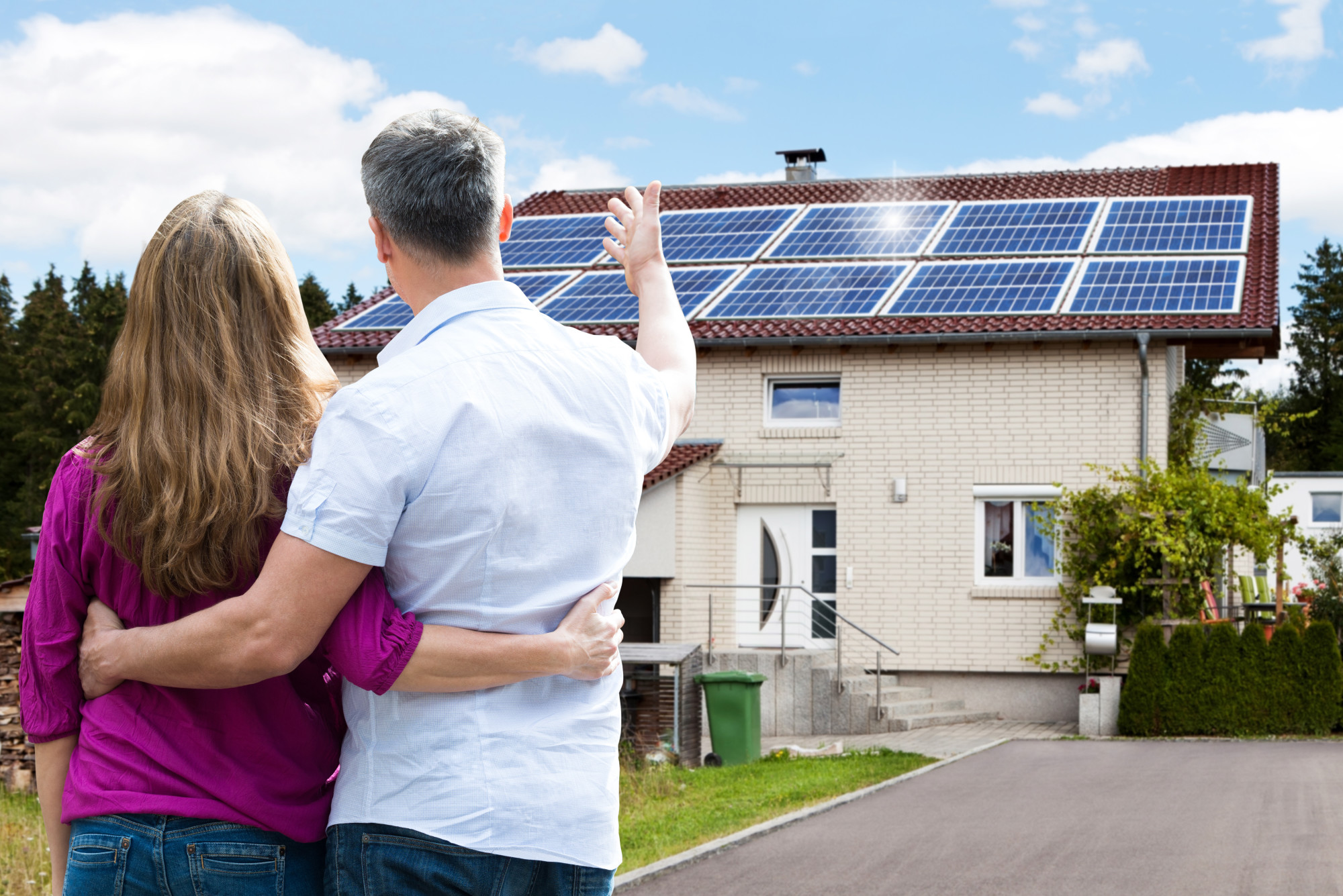 couple standing in front of house that use solar panels