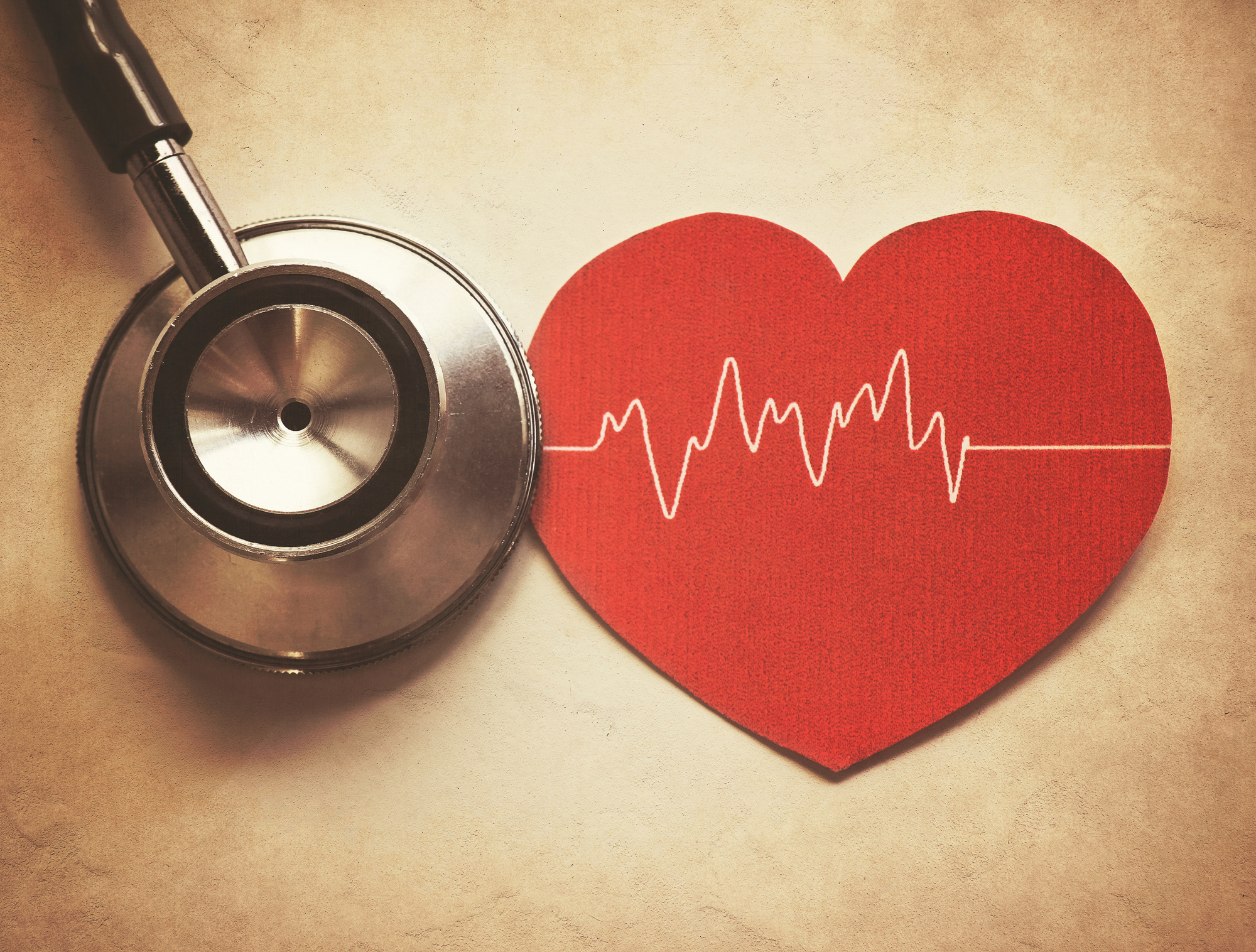 stethoscope and paper heart with heart beat symbol