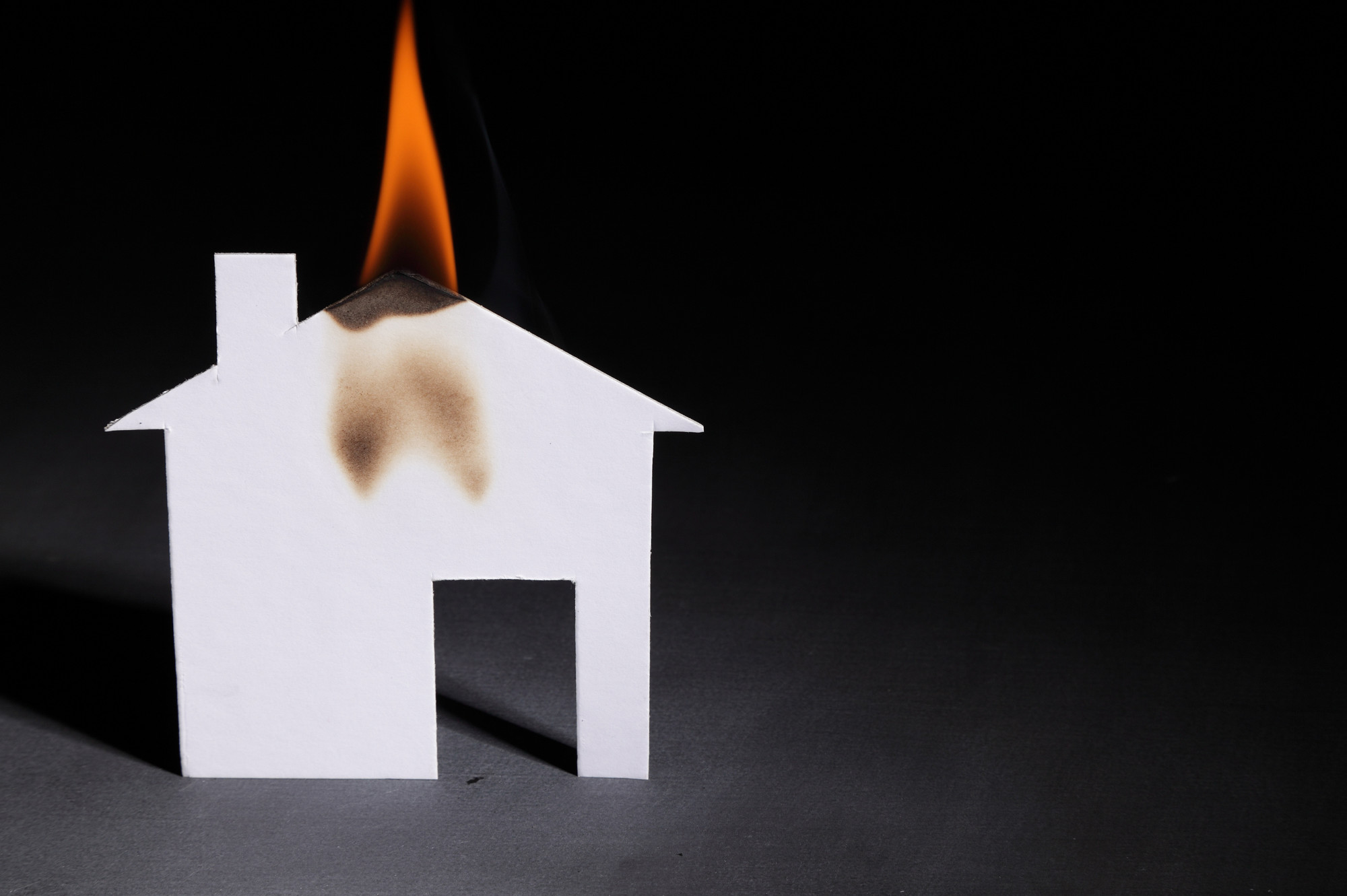 paper house model on fire in black background