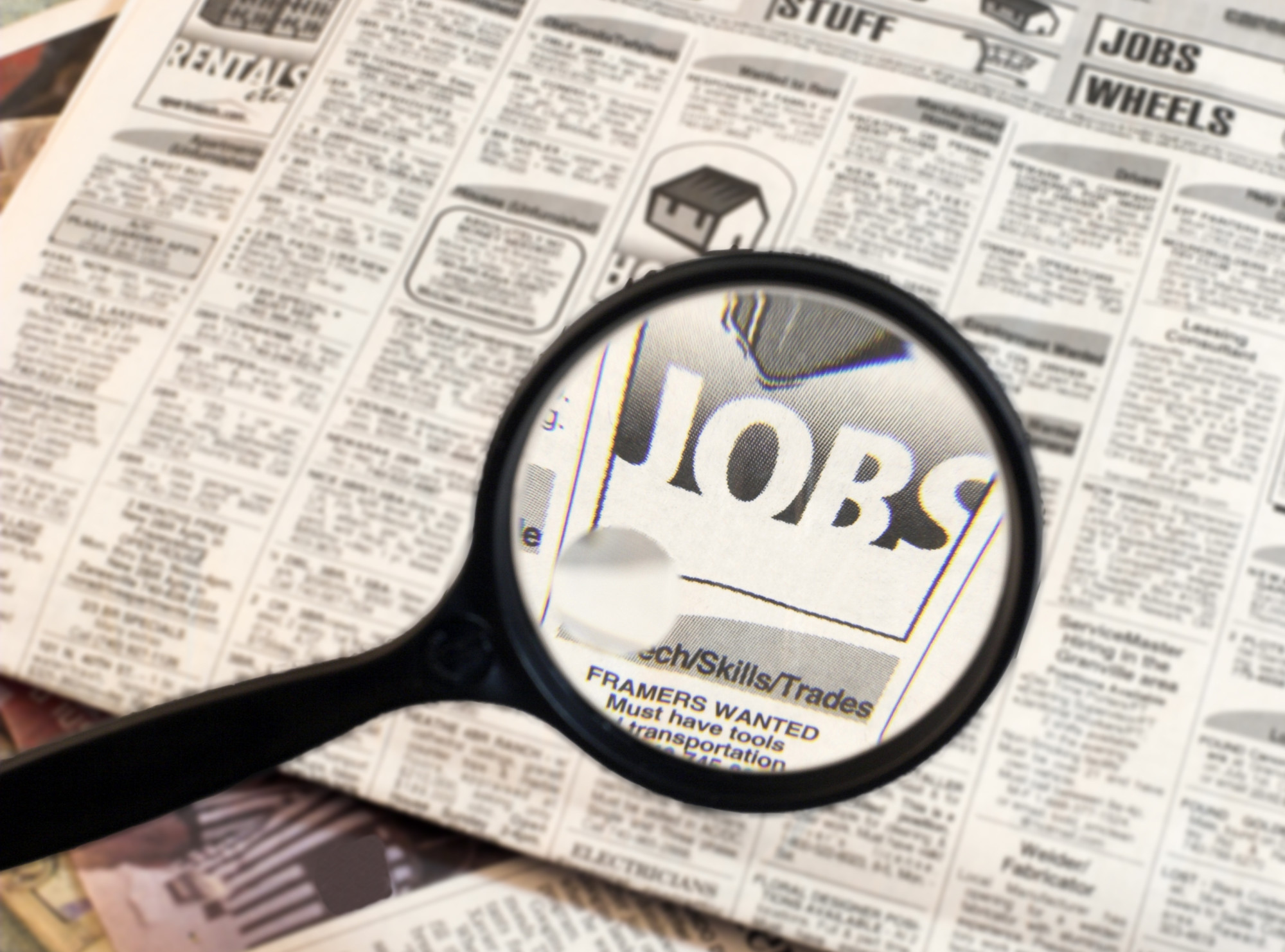 magnifying glass focusing word Jobs in newspaper