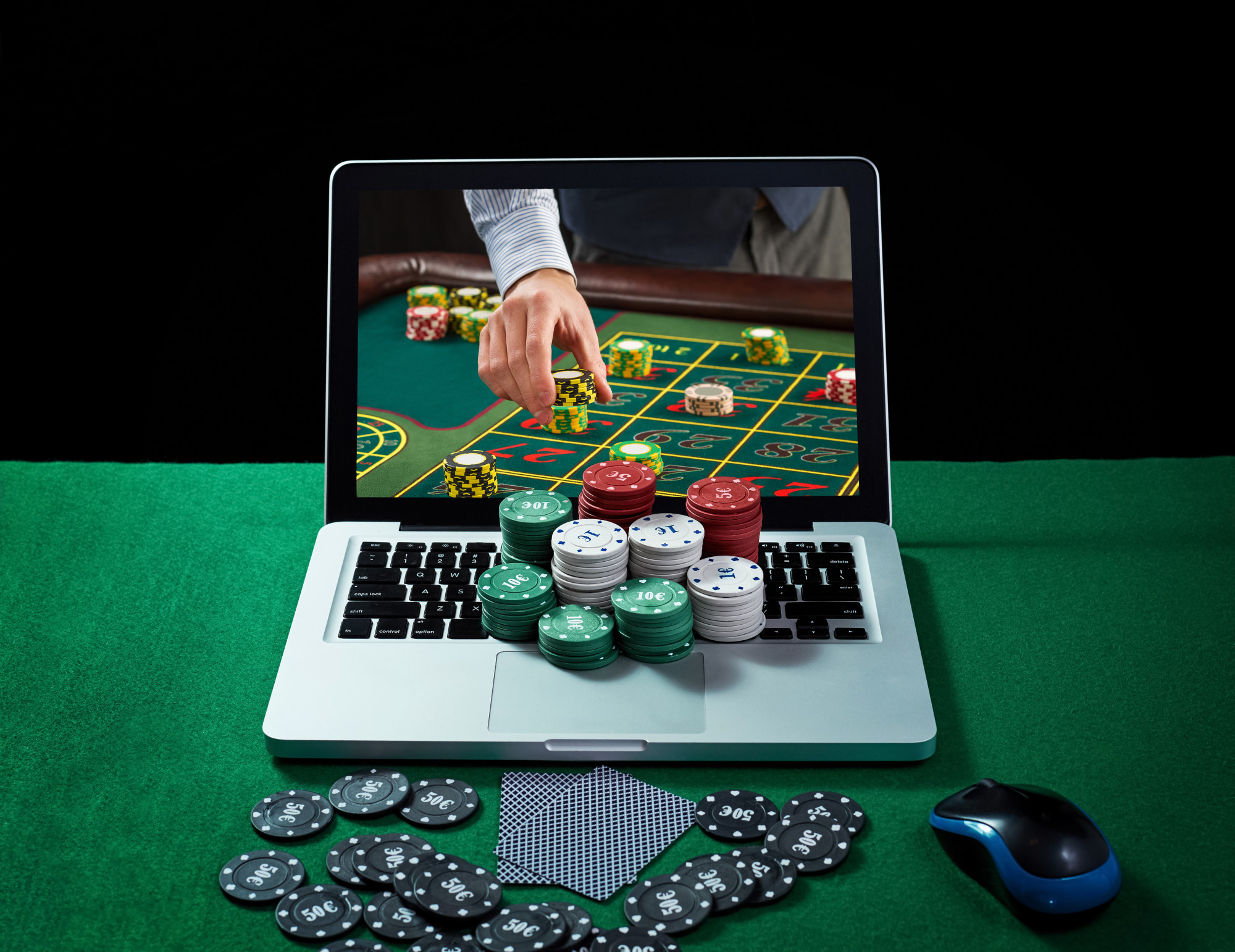 online gambling with casino chips and cards on laptop
