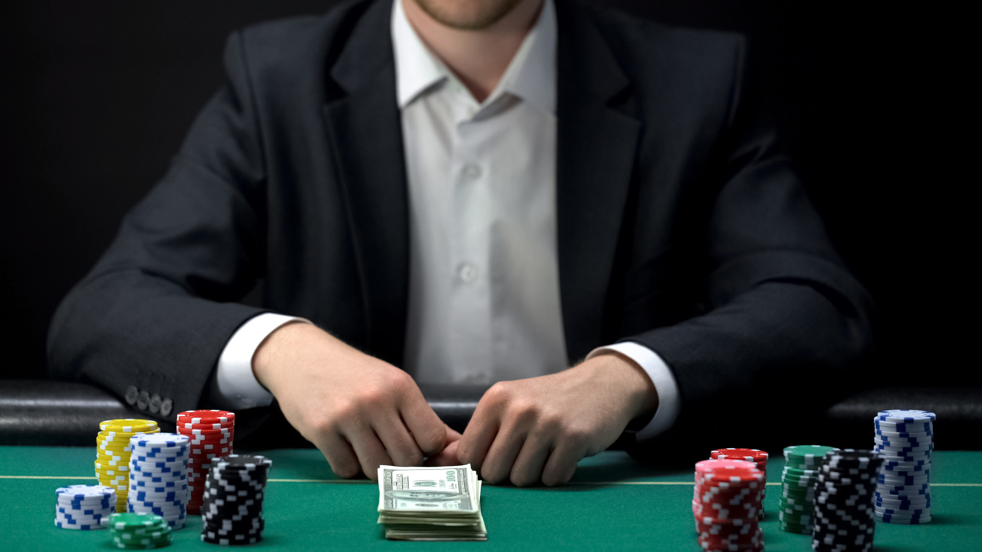male gambler betting all chips and stack of money