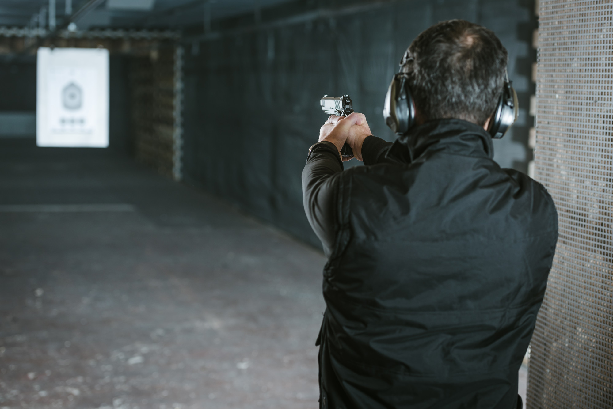 man aiming target in indoor firing range