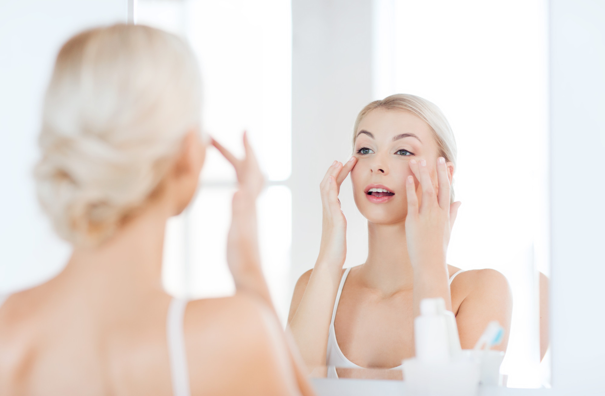 woman facing mirror and applying cream on face