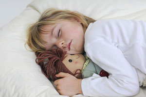 Sleeping child with her doll
