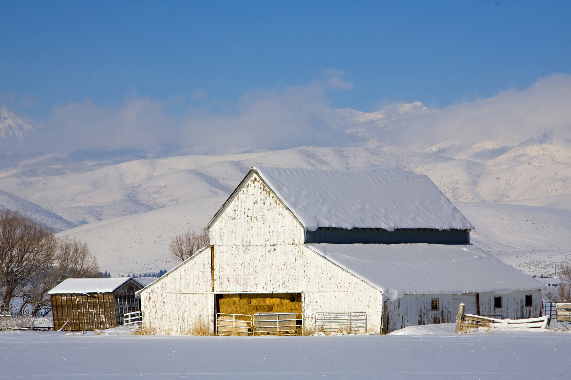 snow-covered farm barn and hills