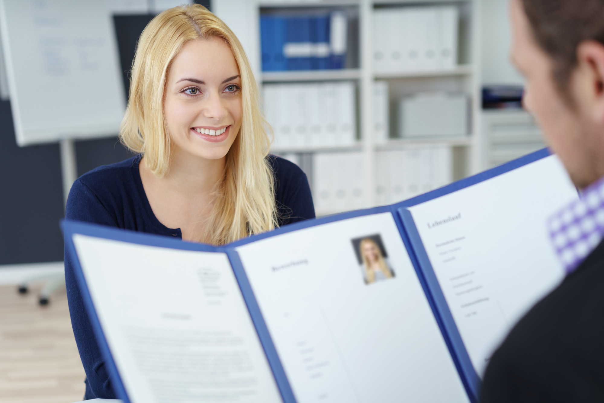 young woman showing her resume on job interview