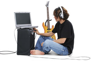Teenager with a laptop and electric guitar